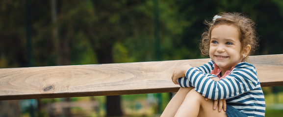 Cute little girl sitting on bench in park, outside