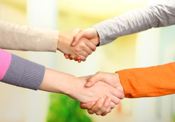 Handshakes on bright background
