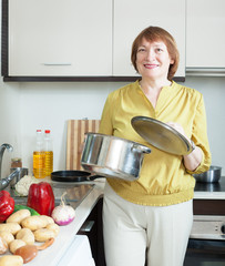 mature housewife  with pan in home kitchen