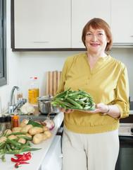 Smiling mature woman cooking  okra