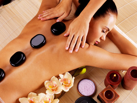 Adult woman having hot stone massage in spa salon