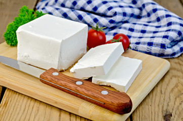 Feta cheese on a board with a knife and tomato