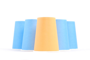 blue recycling paper glasses and one orange standing out on whit