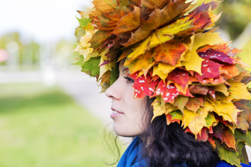 Woman with maple leaves on head