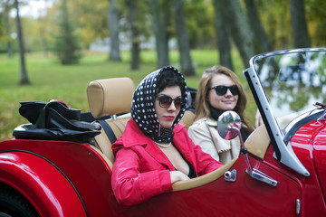 women in black on red retro car