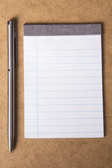 notebook and pen on a brown background