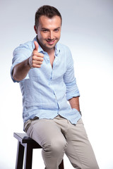seated casual man shows thumb up