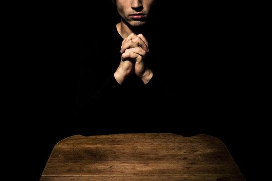Man praying in the dark at table