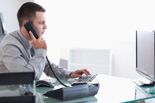 Businessman typing while on the phone
