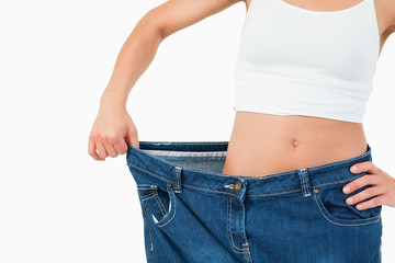 Fit woman wearing too large jeans