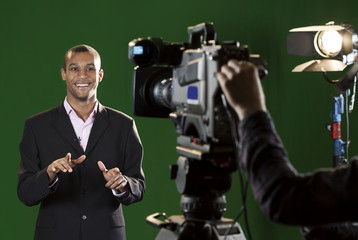 Presenter in studio with TV camera and Camera Operator