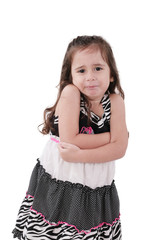 angry little girl in dress with arms crossed on white background