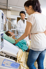 Woman And Doctor Looking At Critical Patient