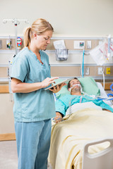Nurse Using Digital Tablet While Patient Resting On Bed