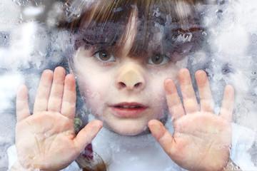 Eiszeit:  Portrait Mädchen klebt mit Gesicht und Händen an Fensterscheibe im Winter