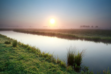 sunrise over river on Dutch farmland