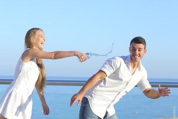 Woman throwing water to her boyfriend
