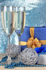 Glasses of champagne with gift boxes on shiny background