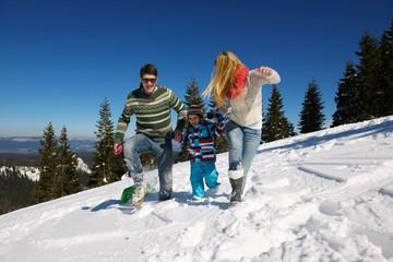 family having fun on fresh snow at winter