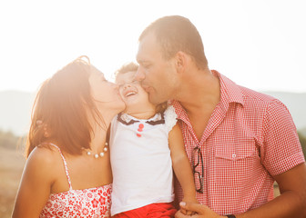 Wall Mural - Happy mother, father and daughter in sunset