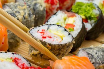 Hot or warm sushi roll in tempura and in chopsticks