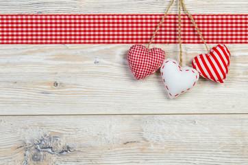 drei Herzen vor Holzbrett