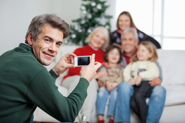Father Photographing Family Through Mobilephone During Christmas
