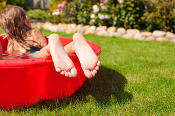 Close-up of a little girl's legs in little red pool