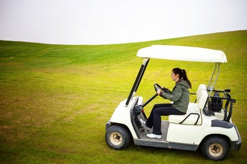 Young woman driving golf cart