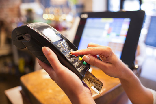 Woman hand with credit card swipe through terminal for sale