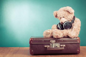 Retro Teddy Bear with headphones on old suitcase
