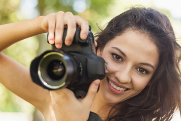 Gorgeous brunette woman holding her camera