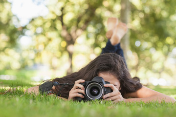 Young woman using her camera for taking a picture lying on a law
