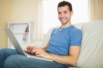 Casual content man sitting on couch using laptop looking at came