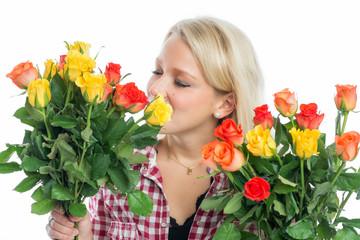 Blonde Frau riecht an Rosen