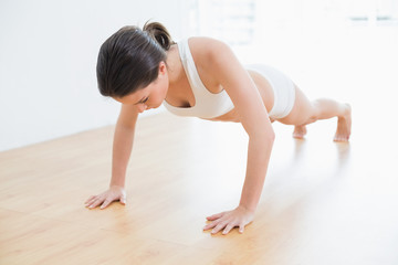 Sporty woman doing push ups in fitness studio