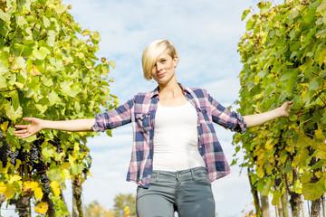 Young woman walking between vine