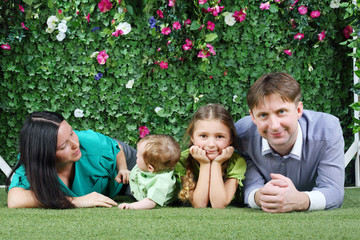 Happy family of four lie on grass near hedge with flowers