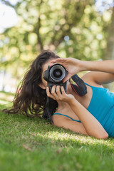 Young brunette woman lying on a lawn taking a picture