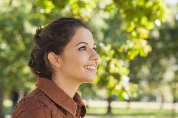 Side view of cute brunette woman wearing a brown coat