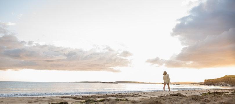Woman in sweater walking on beach