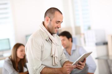 Smiling man in office using digital tablet