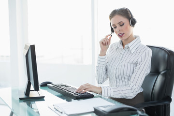 Focused beautiful agent wearing headset sitting at her desk