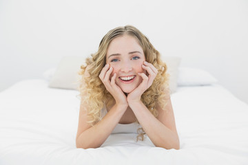 Pretty cheerful blonde lying on bed looking at camera
