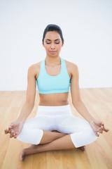 Peaceful slim woman meditating in lotus position