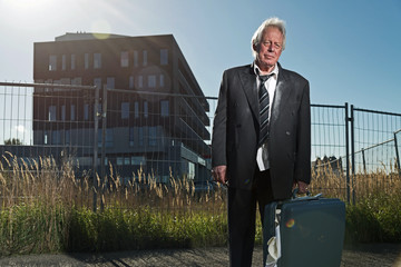 Depressed senior business man without a job standing in front of