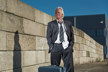 Depressed senior business man with suitcase without a job and ho