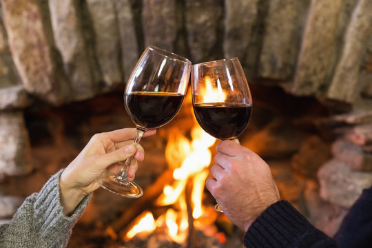 Hands toasting wineglasses in front of lit fireplace