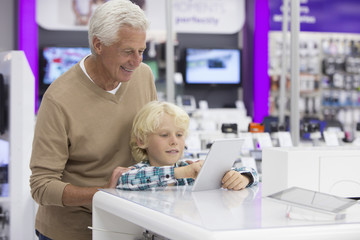 Grandfather watching grandson play with digital tablet in electronics store