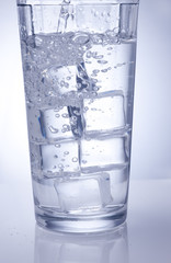 Glass of ice water with bubbles.